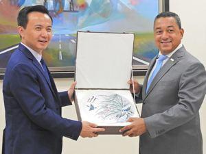 El señor embajador de la República Popular China, Zhang Run y el director general del IDAC Alejandro Herrera intercambian presentes.