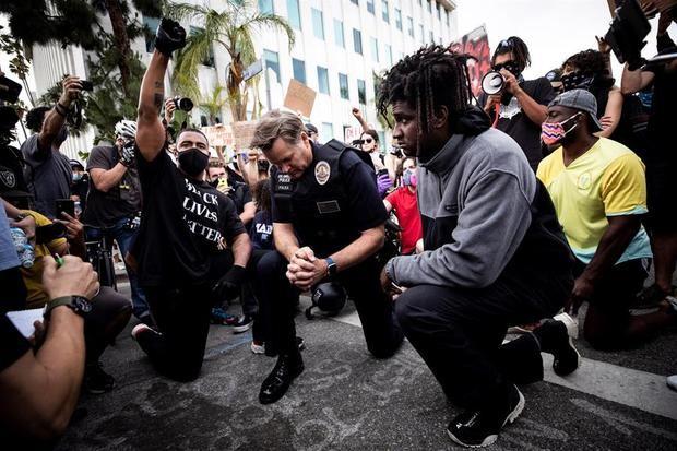 El comandante del LAPD, Cory Palka (C), se arrodilla junto a los manifestantes junto a la casa del alcalde de Los Ángeles, Eric Garcetti, mientras miles de manifestantes salieron a la calle para manifestarse tras la muerte de George Floyd, en Los Ángeles, California, EE. UU.