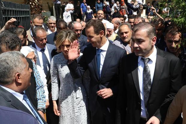 El presidente sirio Bashar Assad (cd) y su esposa Asma (ci) tras votar en el distrito de Douma en Damasco.