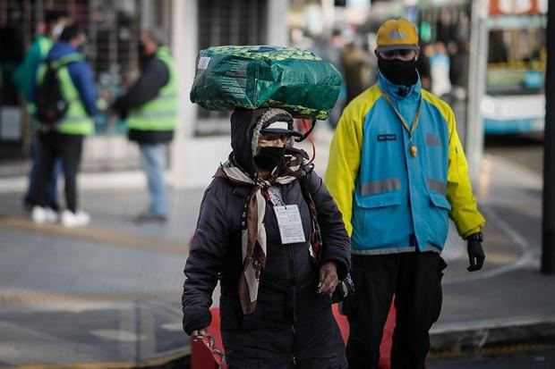 Una mujer pasa este lunes frente a controles de ingreso a la ciudad de Buenos Aires (Argentina).