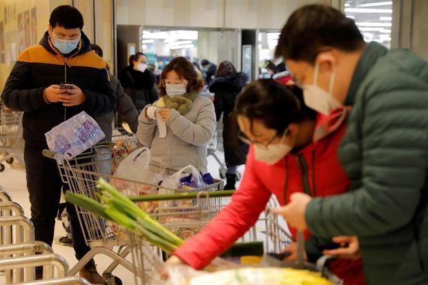 Varios clientes con máscaras protectoras y gafas revisan su factura después de comprar comestibles en un supermercado en un centro comercial en Pekín, China.