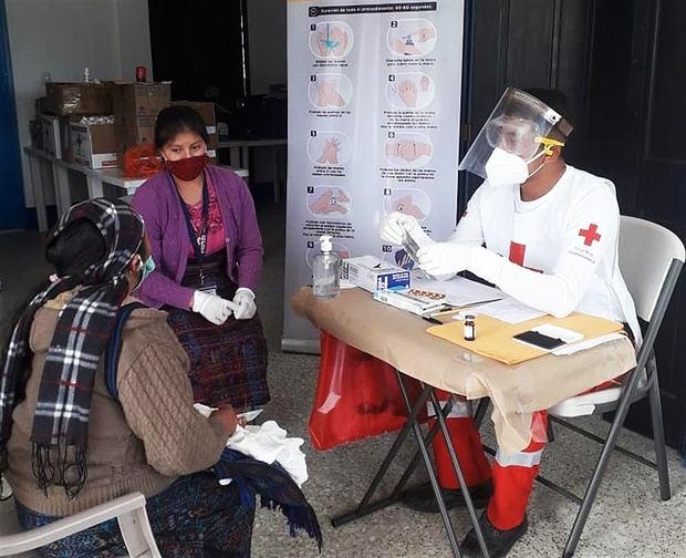 Fotografía cedida por la Cruz Roja Internacional que muestra a uno de sus funcionarios mientras realiza labores de atención médica en medio de la pandemia, en Guatemala.