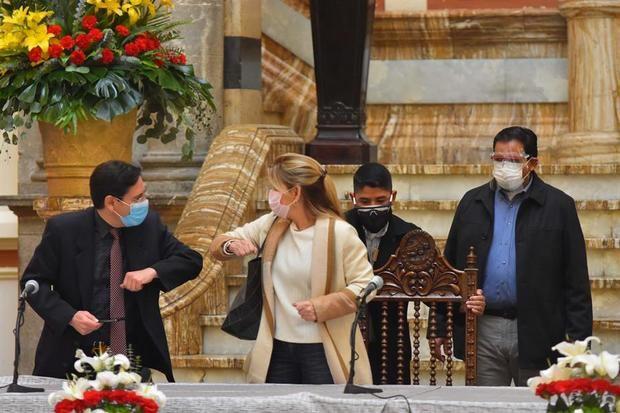 El presidente del Tribunal Supremo Electoral, Salvador Romero (i), y la presidenta interina de Bolivia, Jeanine Áñez (c), se saludan antes de iniciar una mesa de diálogo en el palacio de Gobierno hoy, en La Paz, Bolivia.
