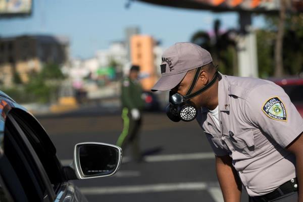 Un agente policial detiene a un automovilista durante el toque de queda este martes, en Santo Domingo (República Dominicana).