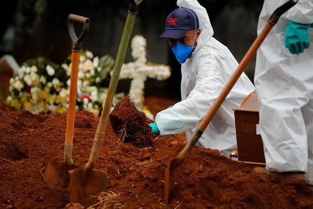 Trabajadores entierran a una víctima de covid-19 en el Cementerio Viola Formosa de Sao Paulo, Brasil.