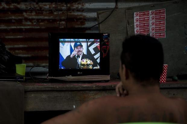 Un hombre observa la pantalla de un televisor en donde aparece el presidente de Nicaragua, Daniel Ortega, durante una transmisión de Cadena Nacional en Managua. Ortega reapareció en televisión, tras 34 días sin dar la cara en público en medio la pandemia por el coronavirus, y defendió la estrategia que ha adoptado su Gobierno y que, según dijo, le ha permitido contener el COVID-19 en nueve casos, con solo un fallecido.