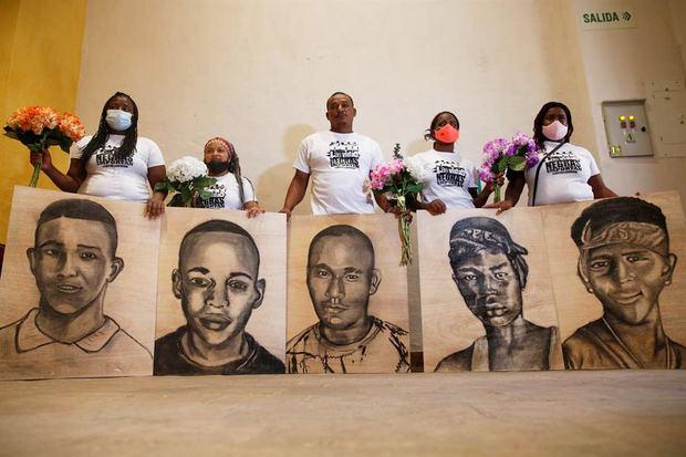 Familiares de las víctimas de la masacre de Llano Verde, sostienen hoy retratos suyos durante un acto conmemorativo, en Cali (Colombia).