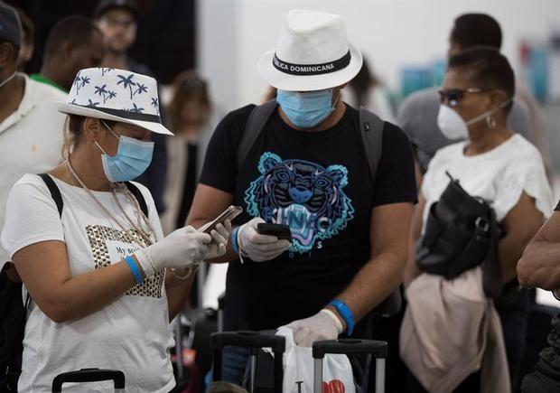 Pasajeros hacen fila para abordar este viernes el primer vuelo ferry fletado por la compañía Iberia para sacar de la República Dominicana a los españoles que se han encontrado sin posibilidad de salir del país a causa de la crisis del coronavirus, el cual despegó desde el aeropuerto internacional de Las Américas.