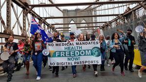 Decenas de activistas y personas antivacunas caminan durante una marcha antivacunas hoy, en el puente de Brooklyn, Nueva York, EE.UU.