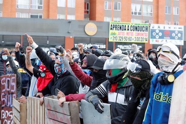 Manifestantes utilizan hoy escudos improvisados durante una protesta en el día 13 del Paro Nacional contra el Gobierno de Iván Duque, en Bogotá, Colombia.