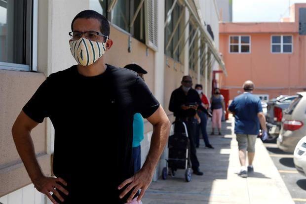 Un hombre usa una mascarilla de protección mientras espera en fila en San Juan, Puerto Rico.