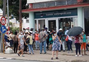 Varias personas esperan su turno para entrar a un banco hoy, en La Habana, Cuba.