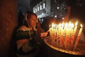 Una mujer enciende velas en la iglesia de la Natividad de Belén, donde la tradición cristiana afirma que nació Jesús de Nazaret, en la ciudad cisjordana de Belén.