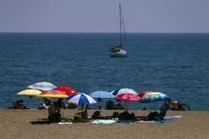 Bañistas bajo las sombrillas en la playa de La Malagueta de la capital de la Costa del Sol.