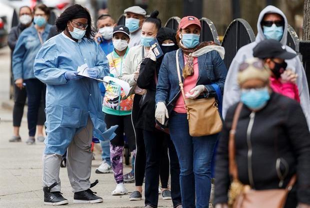 Un trabajador de la salud habla con las personas que esperan en la fila en una ubicación de prueba comunitaria COVID-19 recientemente inaugurada en Nueva York, EE. UU.