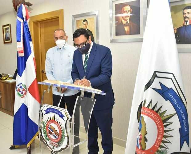 El embajador del Reino Unido Mockbul Ali OBE, firma el libro de personalidades durante su visita a la DNCD.