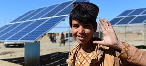 Un joven posa en frente de paneles solares que proveen energía para transportar agua en Herat, Afganistán. El corazón de la juventud