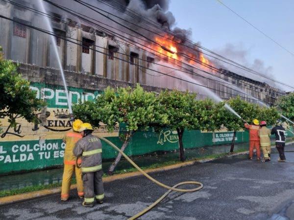 Bomberos tratan de sofocar incendio en una colchonería en la capital.