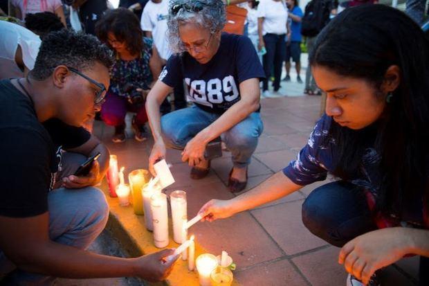 Manifestantes mientras encienden velas en señal de protesta.