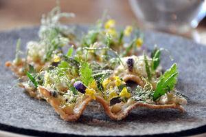Aperitivo con unas finas tostadas de huevas de rape, acompañadas con flores violetas y polvo de vinagre, lo cual le da la apariencia de un jardín recién tocado por el rocío.