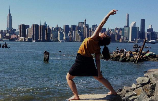 Postura del guerrero pacífico en yoga con la silueta de la ciudad de Nueva York de fondo.